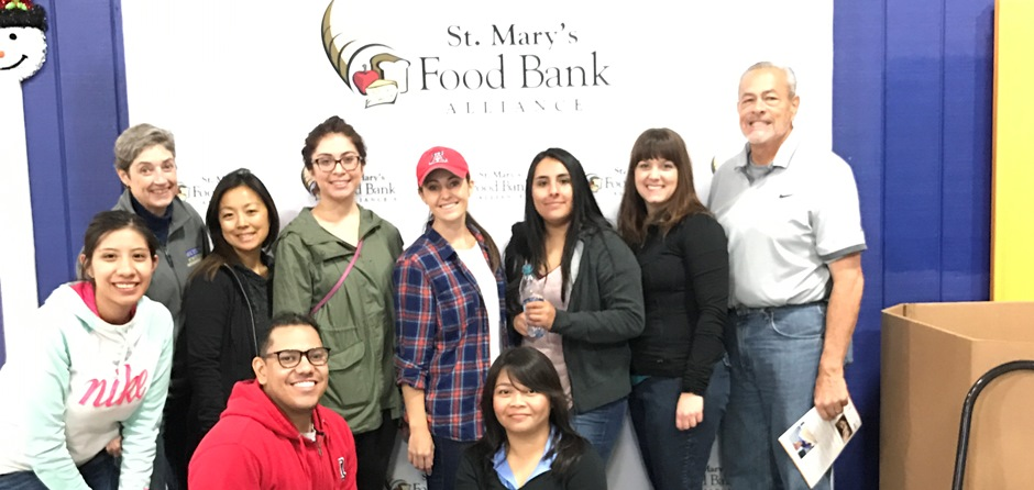 students in the Phoenix Urban Service Learning course pose at St Mary's Food Bank while preparing emergency food boxes