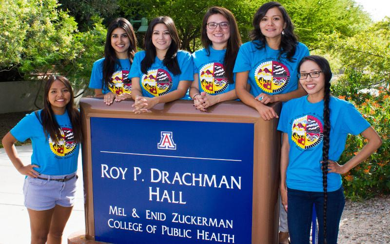 Six students gather around the Drachman Hall sign