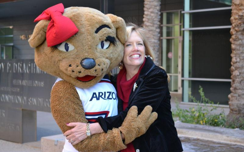 Chris Tisch and Wilma Wildcat embrace in front of Drachman Hall.