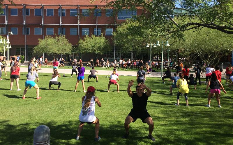 A group of people exercising in a grass field