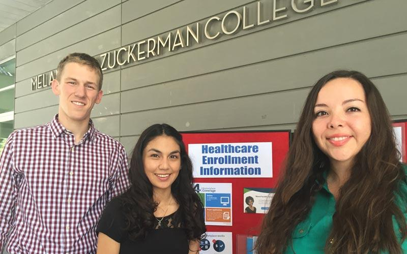 Photo of three students standing in front of Healthcare Enrollment Information poster board