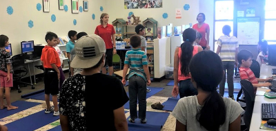 The children learn yoga for stress reduction.