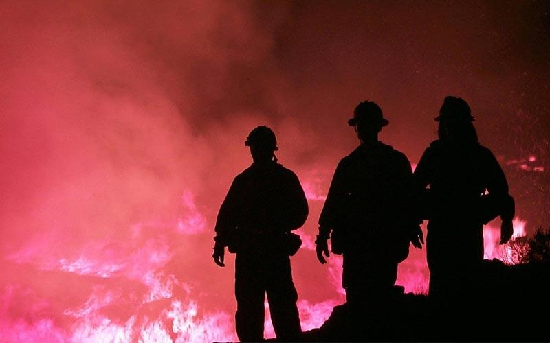 Firefighters in silhouette in front of a large fire