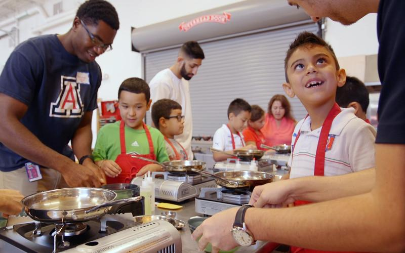 Campers working with adults to cook healthy meals.